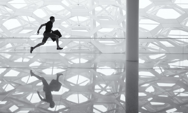 Mann rennt mit Aktentasche und kurzer Hose durch moderne Halle.