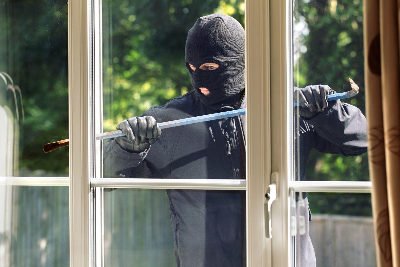 Einbrecher mit Brecheisen am Fenster