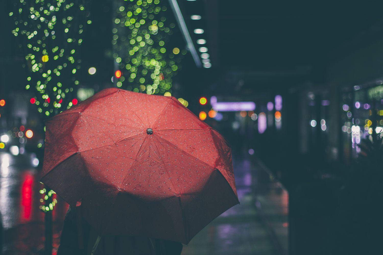 Person mit Regenschirm in einer Stadt bei Nacht.