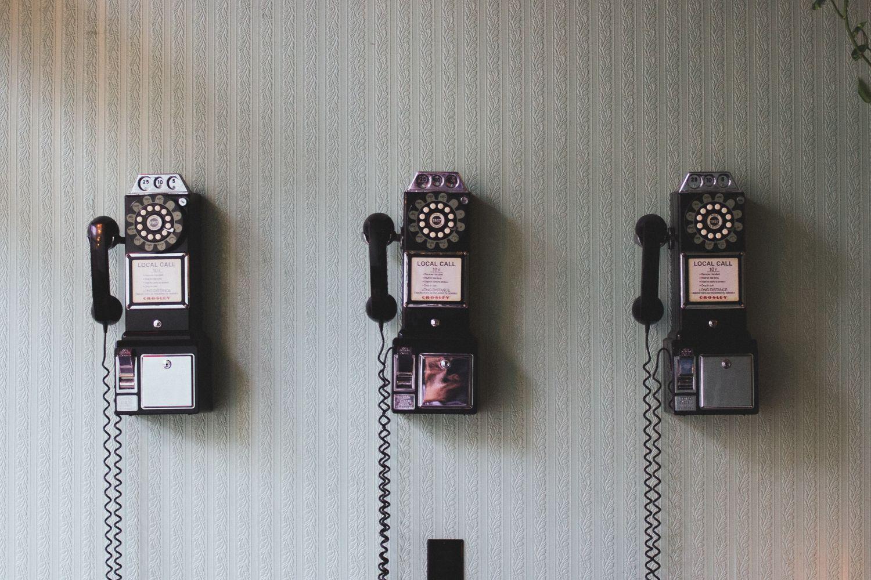 Drei historische Telefone hängen nebeneinander an einer Wand.