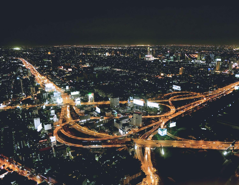 Nachtaufnahme einer Stadt von oben mit stark beleuchteter Hauptverkehrsader