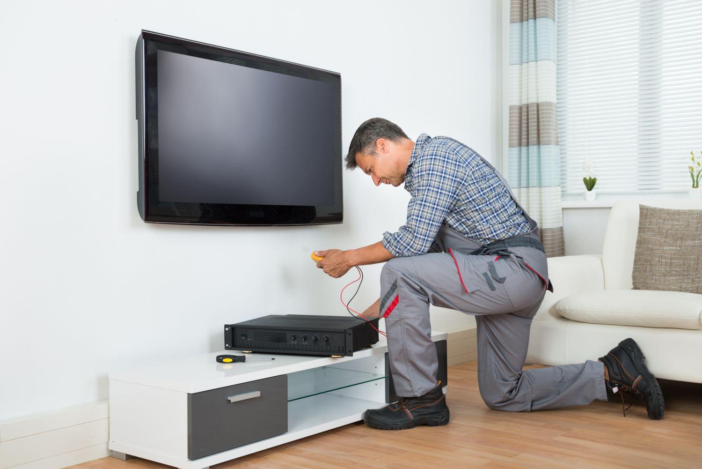 Ein Mann montiert eine Fernsehanlage